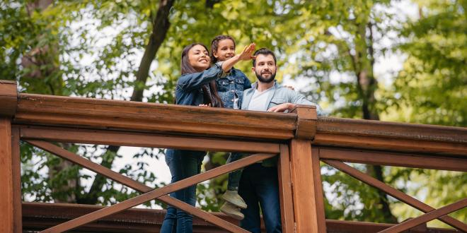 Happy interracial family standing on wooden bridge, while mother pointing somewhere